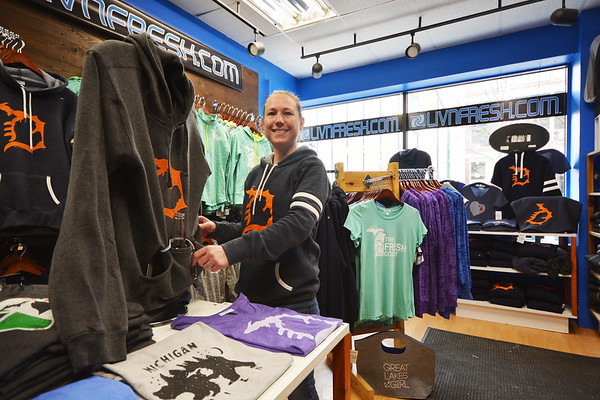 "Record-Eagle/Dan Nielsen Store manager Cyndi Kremer demonstrates the ""beer koozie"" built into some of Livnfresh's hoodies."