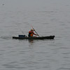 A kayaker with an ice chest and a fishing pole.  Sounds like my idea of a good day.