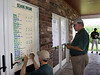 Scores are entered onto the scoreboard as the golfers come in during the Saginaw District Golf Association Tournament qualifier Sunday at Green Acres Golf Course, Bridgeport.