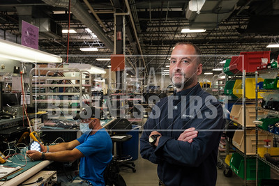Michael Denault inspects a light behind Pat Pierce, manufacturing and engineering manager for Astronics.