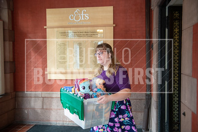 Danielle Stoner a foster case planner for Child and Family Services moves a box of toys to a new facility.