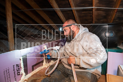 Supportive Services worker Angelo Guzzetta fills the gaps in the insulating foamboard in the attic of one of the non-profit's weatherization project homes.