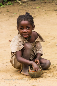 Young Ombo girl playing with old tin cans making mud pies?  Republic of Congo , Ndzehi Concession Department of Cuvette-Quest.