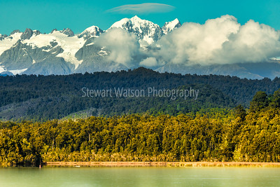Layers of nature water trees forest and snow covered Southern Alps of New Zealand