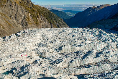 Check out the enormity of the Southern alps glacier with the red helicopter flying below