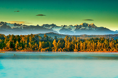 Dramatic light on the Peaks of the Southern Alps behind the forest and Okarito Lagoon