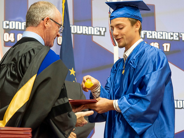 West Noble graduate Brockton Miller, right, hand high school principle Dr. Gregory Baker a duck in exchange for his diploma during Friday's  West Noble High School Class of 2021 Commencement at West Noble High School in Ligonier. The duck is a symbol of the class of 2021's class prank where they filled the pond near the school with rubber ducks.