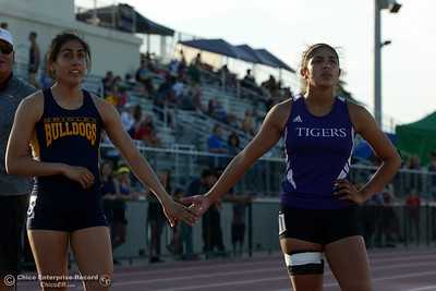 Gridley's Stephanie Cardenas, left, and Oroville's Kaitlin Paul, right, share a low-five as they look to the scoreboard for their times Friday, April 21, 2017, during he West Valley Invitational at Harrison Stadium in Oroville, California. Cardenas won both the 100-meter and the 300-meter hurdles. (Dan Reidel -- Enterprise-Record)