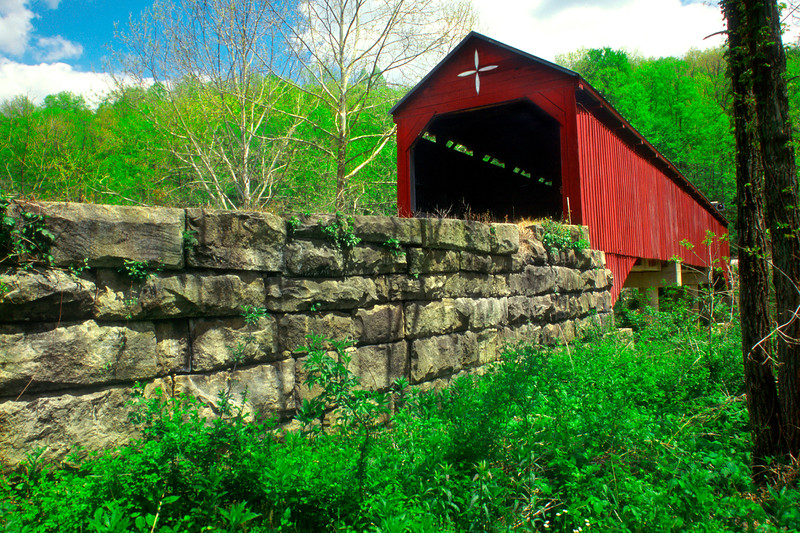 CARROLLTON COVERED BRIDGE<br />   The second longest and third oldest covered bridge in West Virginia, this span was built in 1856, by contractors Daniel and Emmett J. O'Brien of Beverly.  About 140 feet in length and 16 feet in width, this bridge is one of three examples in the state of the patented Burr Arch truss structure.  The bridge was upgraded in the early 1960's but the covering and the sides of the old bridge were left intact.  It is schedule to be completely restored in 2003.<br />   To locate it, from the junction of US routes 119 and 250 in Philippi, take route 119 south 6 miles to secondary route 36 (Carrollton Road).  Turn left and drive 7/10 mile directly to the bridge over the Buckhannon River.