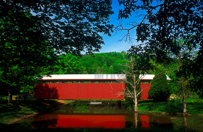 """STAATS MILL COVERED BRIDGE<br />   Built in 1887 by H.T. Hartley, this bridge spanned the Tug Fork of Big Mill Creek at Staats Mill, about 9 miles southeast of Ripley.<br />   Hartley used the patented Long truss system to construct the 97-foot long and 11-foot wide span.  The bridge was originally built in the area settled by Abraham and Ann King Staats, whose grandson Issac built Staats Mill.<br />   The bridge was moved in 1983 to its present location at Cedar Lakes state FFA-FHA camp near Ripley.  It now serves as a walking bridge and its maintenance is the responsibility of the Cedar Lake Conference Center.<br />   To locate the bridge, from downtown Ripley at the junction of US route 33 and secondary route 21, take route 21 south for 9/10 mile to a small sign on the right, which says """"Cedar Lakes Road"""".  Turn left and drive 1.7 miles to Cedar Lakes, the bridge sits over a pond inside the camp."""