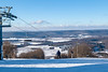 View of skiers from top of mountain on winter day