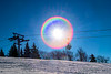 Circle of light from the sun behind the ski lift