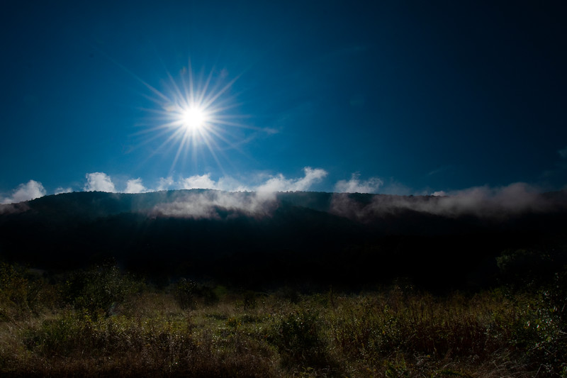 Sun highlighting clouds top of mountain