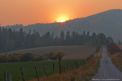 near the house, smoke from a Yellowstone fire fills the air as the sun sets.