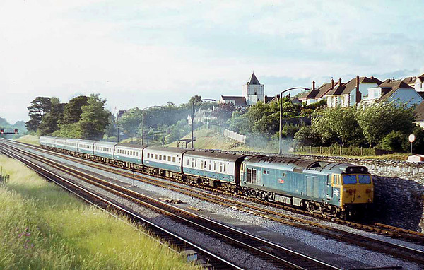 An inidentified Class 50 in 'as-built' condition heads a Paddington to Paignton service near Aller Junction in 1977.