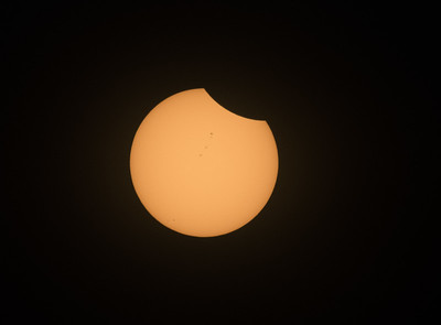 The eclipse has started, as the moon moves across the face of the sun.  Note the line of sunspots in the upper half of the sun's face, plus some more sunspots in the lower left quadrant.  This was taken about 80 minutes before totality.