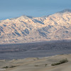 The Mesquite Flat Sand Dunes and sunlit mountains near sunset.