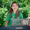Elliana Tweedie of Westford smiles big after preforming a song on the piano for the crowd attending the Westford Strawberry and Arts Festival. SUN/Caley McGuane