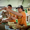 Colby Fleckner and Tara Lynch hand out homemade bagels from Bagel Alley in Nashua to customers at the Westford Strawbery and Arts Festival. SUN/Caley McGuane