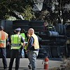 Westford Police officers talk with members of the Westford Highway Department at the scene of a dump truck rollover at the intersection of Lowell and Providence roads Friday morning.