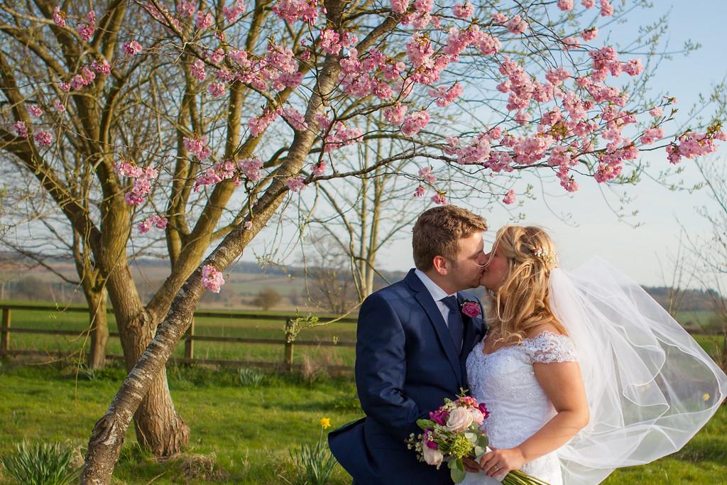 Bride & groom kissing under a blossom tree.