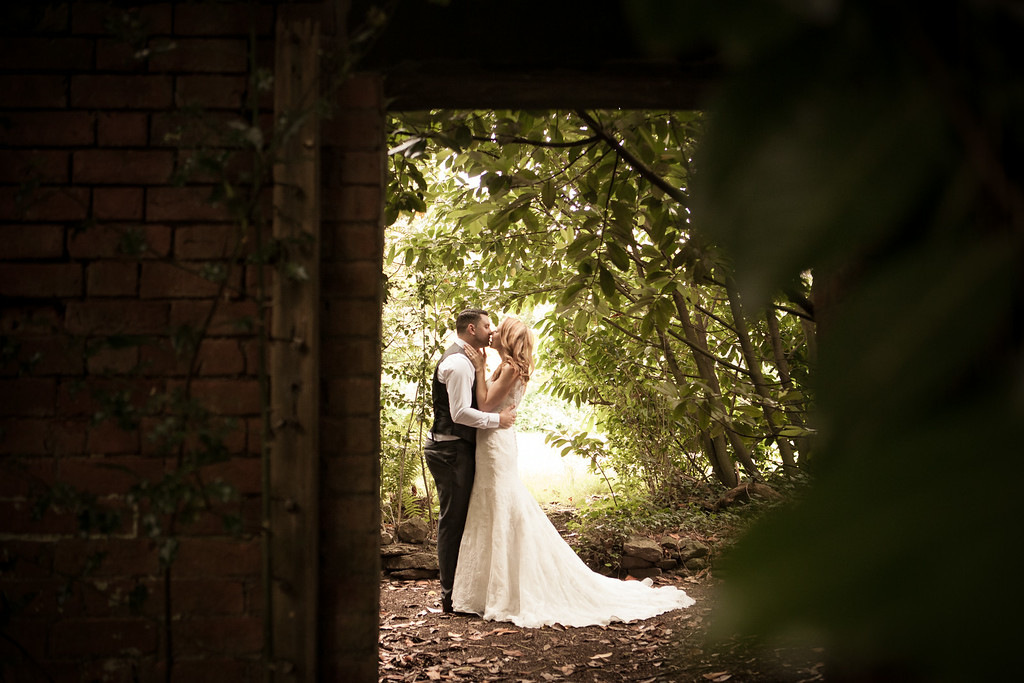 bride and groom kissing in the sunlight through a gap in a wall surrounded by trees.