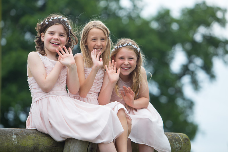 bridesmaids smiling and waving at the camera sat on a climbing frame.