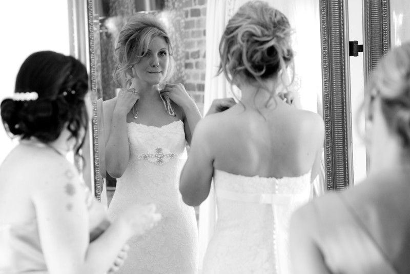 bride looking in mirror choosing which necklace to wear with bridesmaids looking on.