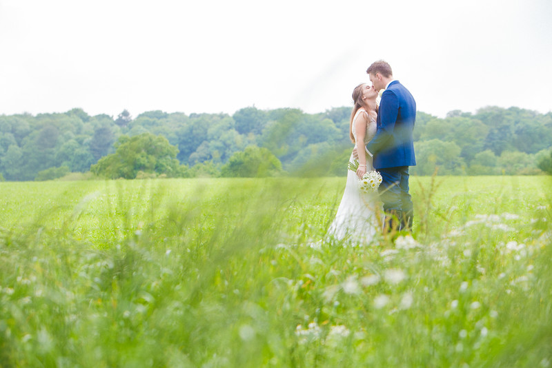 Bride and groom kissing in a field on a summers day.