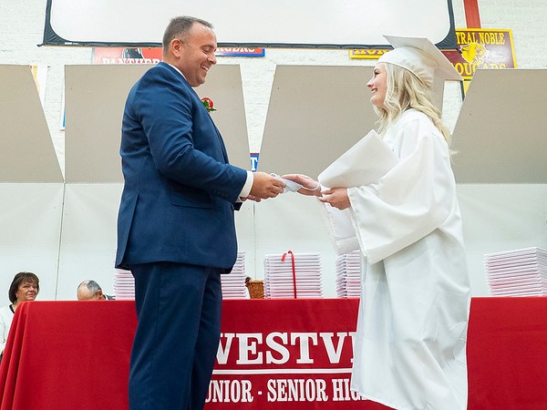 Westview Senior Class of 2021 Kaylee Adelmann, right, hands her mask in exchange for a hand shake to High School Principal  Dr.  Rich Cory during Friday's commencement ceremony at Westview Jr./Sr. High School.