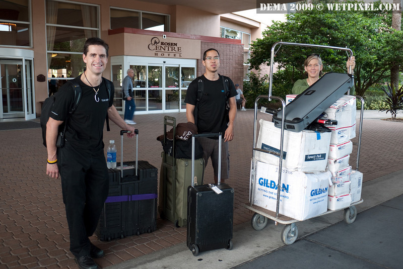Shawn Heinrichs, Adam Lau and Michaela Brockstedt haul boxes to DEMA