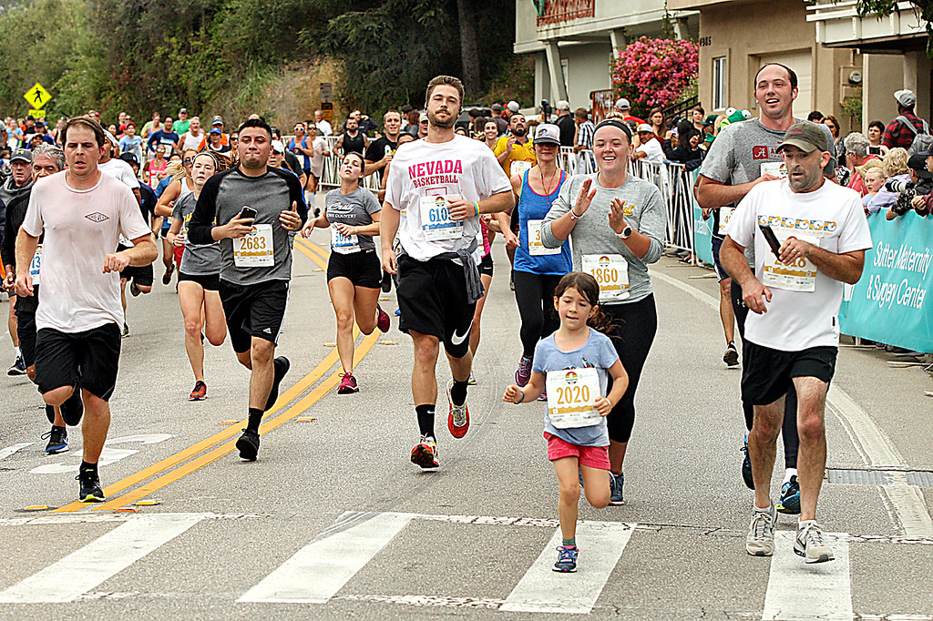 . Wharf to Wharf runners--all ages and sizes--approash the finish line in Capitola Village. (Dan Coyro -- Santa Cruz Sentinel)