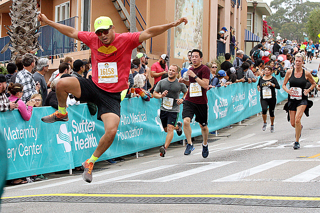 . A Wharf to Wharf runner leaps across the finish line. (Dan Coyro -- Santa Cruz Sentinel)