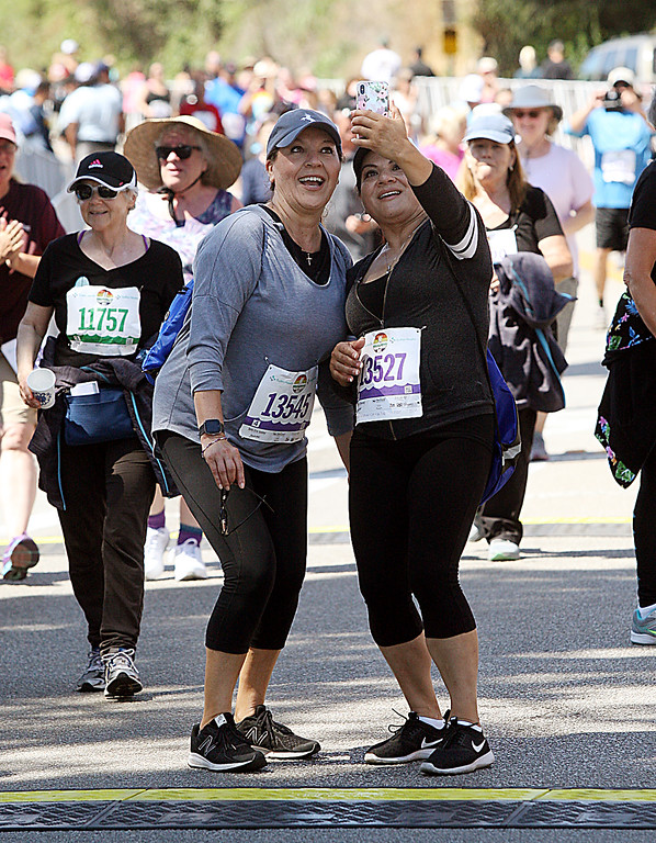 . Two runners record their completion of the race with a selfie at the finish line. (Dan Coyro -- Santa Cruz Sentinel)