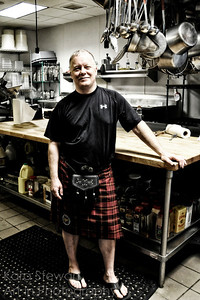 August 12, 2012  Dave at Work  This is another one of my dearest friends that I was able to visit with on my recent trip back to West Chester (PA). We were getting ready for his and his brother's birthday party and stopped in to his work to pick up his cake (he's a chef).  He was dressed for the party in his kilt (as was his brother and many others) since he plays in Brian Boru Pipes and Drums http://www.brianborupipesanddrums.org/index.htm .  Band in junior high is actually how we met - he was a drummer back then too!   At any rate, I took the opportunity of him being both in his kilt and at work to take this portrait of him. Since I haven't used my camera much at all in the last few months, the quality of the shot wasn't good, so I played with it. I ended up quite liking the bleach bypass filter on Color Efex for this image.