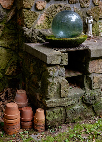 Retirement + a new camera = spending more time walking around the property on Photo Safari. Detail, patio barbecue with flower pots, Japanese glass float, and porcelin angel.