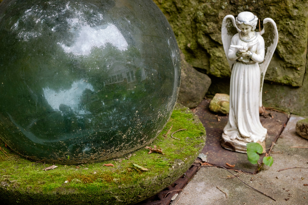 Garden detail. Japanese glass fisherman's float and porcelin angel.