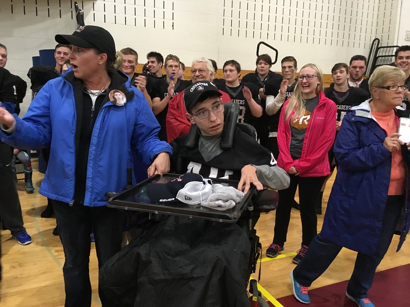 The Groton-Dunstable High School football team and other supporters gather behind Lain MacDonald