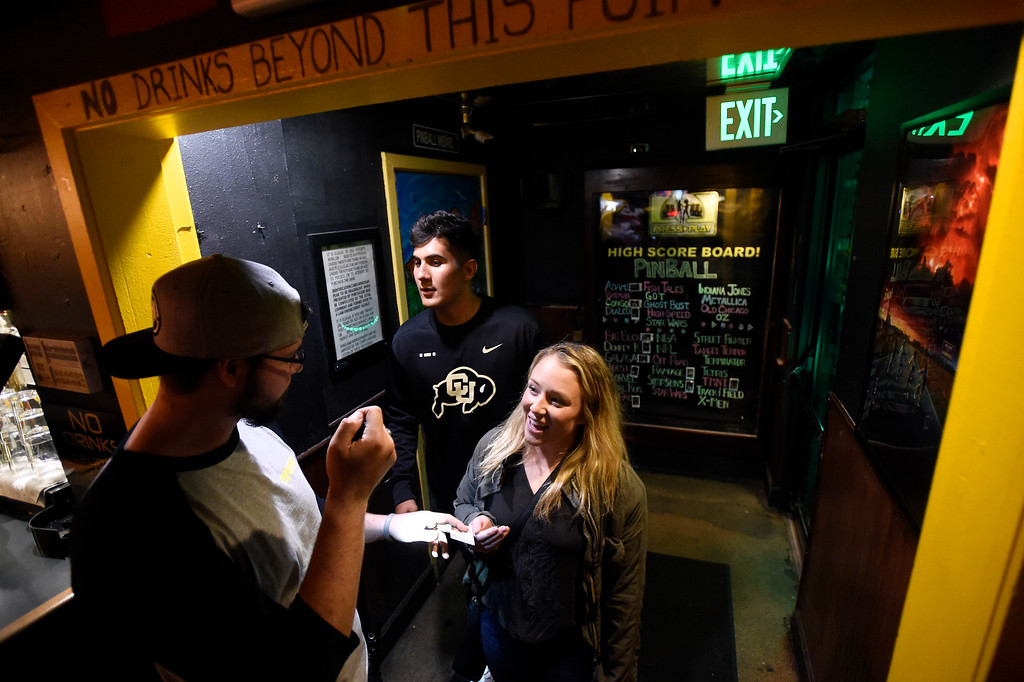 . BOULDER, CO - OCTOBER 25, 2018: Bouncer Philip Stahly checks the ID\'s of University of Colorado senior Danielle C. and junior Ethan, both who declined to give their last name, at the Press Play Bar on Thursday night on Pearl Street in Boulder. For more photos of people drinking and hanging out at the bars near Pearl Street go to dailycamera.com (Photo by Jeremy Papasso/Staff Photographer)