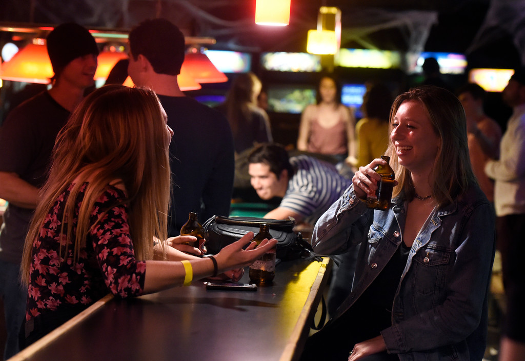 . BOULDER, CO - OCTOBER 25, 2018: University of Colorado seniors Riley, at right, and Natalie, both who declined to give their last names, share a laugh while hanging out at the Press Play Bar on Thursday night on Pearl Street in Boulder. For more photos of people drinking and hanging out at the bars near Pearl Street go to dailycamera.com (Photo by Jeremy Papasso/Staff Photographer)