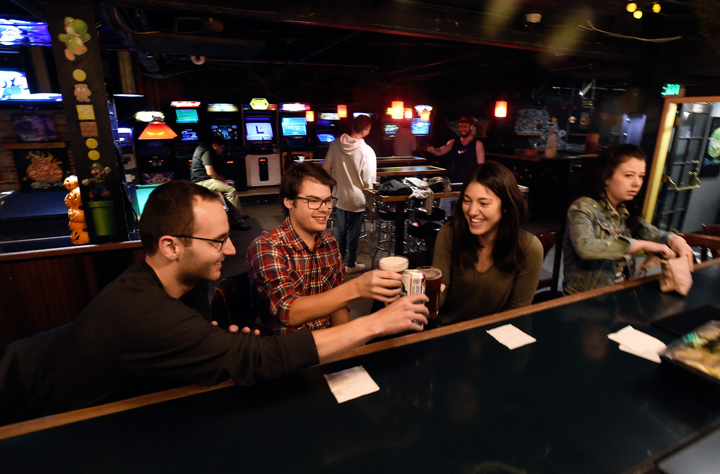 . BOULDER, CO - OCTOBER 17, 2018: Alex Sloan, left, Jesse Litton and Sanette Sloan cheers each other after ordering beers at the Press Play Bar on the Pearl Street Mall on Wednesday night in Boulder. For more photos of younger people drinking on Pearl Street go to dailycamera.com (Photo by Jeremy Papasso/Staff Photographer)
