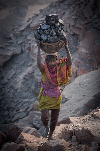 Every morning at least a hundred people carry away illegally collected coal from several coalmines. Also a lot of children do this work. <br /> Young girl carrying coal on her head.