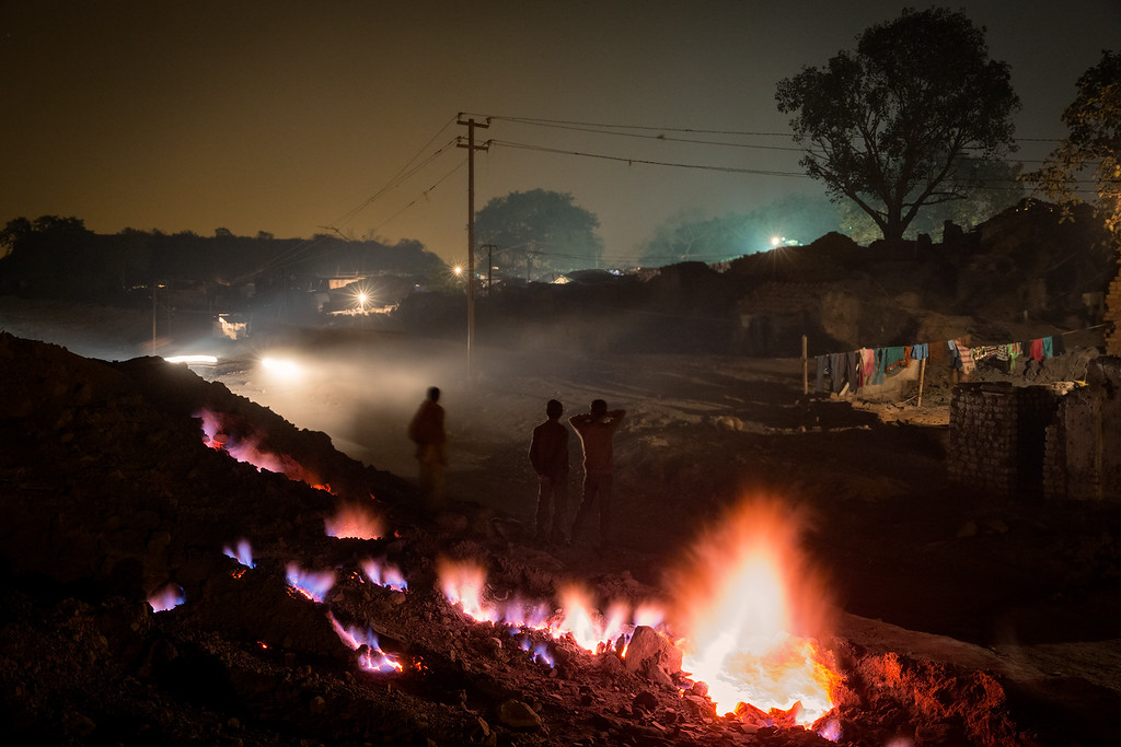 In the city of Jharia and surroundings, an underground fire has been burning since 1916 - or even longer according to the locals. The fire probably started when abandon coalmines was not properly closed. The fire evolved in to more than 70 underground fires. The inhabitants use the fire to warm themselves on cold winter nights, to dry clothes and sometimes even cook food. The crack on this photo is only about 200 meter away from the village of Bokapahti, where several families live. The crack appeared first time in 1976, then the government came and closed it with rocks and sand. But in 2001 the crack opened up again.