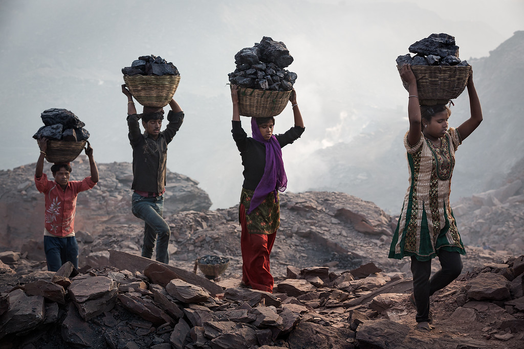 Every morning at least a hundred people carry away illegally collected coal from several coalmines. Also a lot of children do this work. Here people are carrying coal on their head.