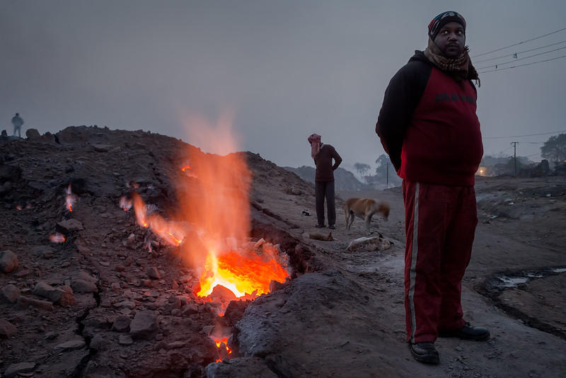 In the city of Jharia and surroundings, an underground fire has been burning since 1916 - or even longer according to the locals. The fire probably started when abandon coalmines was not properly closed. The fire evolved in to more than 70 underground fires. The inhabitants use the fire to warm themselves on cold winter nights, to dry clothes and sometimes even cook food. The crack on this photo is only about 200 meter away from the village of Bokapahti, where several families live. The crack appeared first time in 1976, then the government came and closed it with rocks and sand. But in 2001 the crack opened up again.<br /> Early morning and it's bit chilly, so people use the heat from the burning coal to warm themselves.