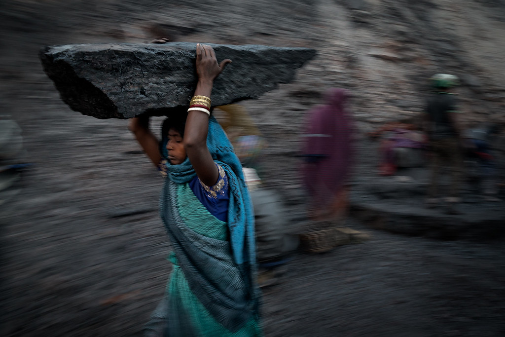 Every morning at least a hundred people carry away illegally collected coal from several coalmines. Also a lot of children do this work. <br /> Woman carrying heavy block of coal on her head.