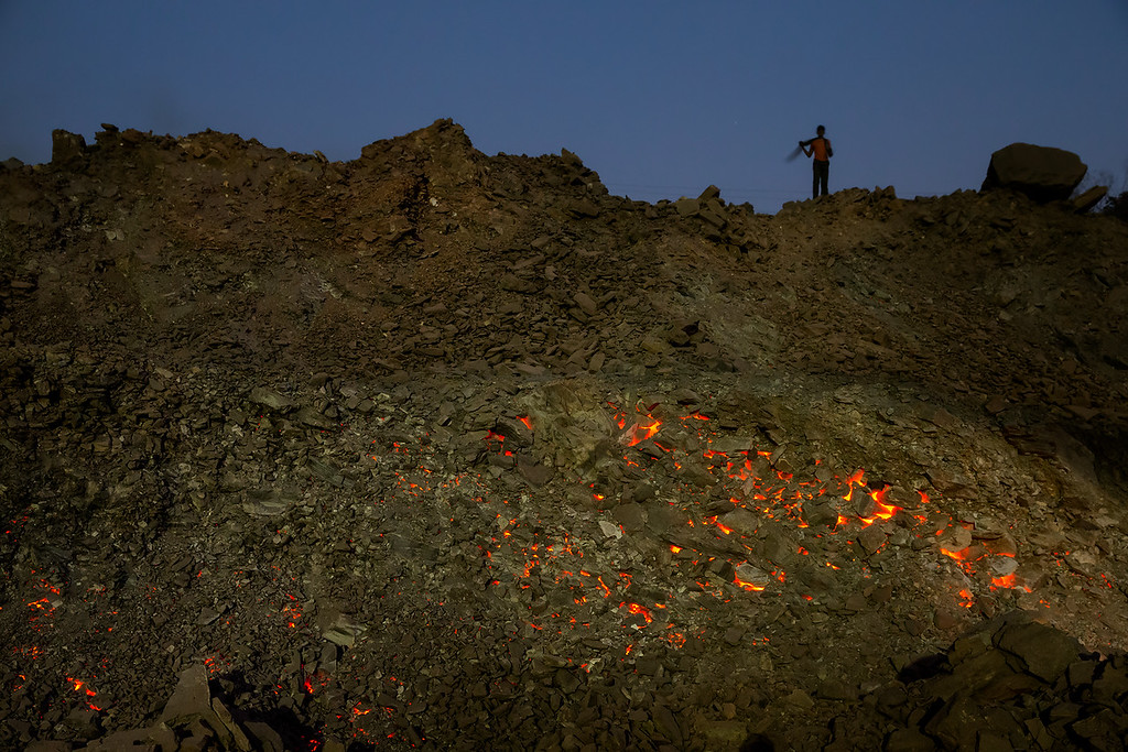 In Jharia, India, the underground coal has been burning for more than 80 years – some say more than 100 years – and it is still burning. Actually, it has never been worse than now. The earth is literary on fire. Whole mountains are burning, houses disappear and people are dying. Walking on top of the burning coal almost melted the soles of my sturdy shoes. Here a guard in a coalmine is watching.