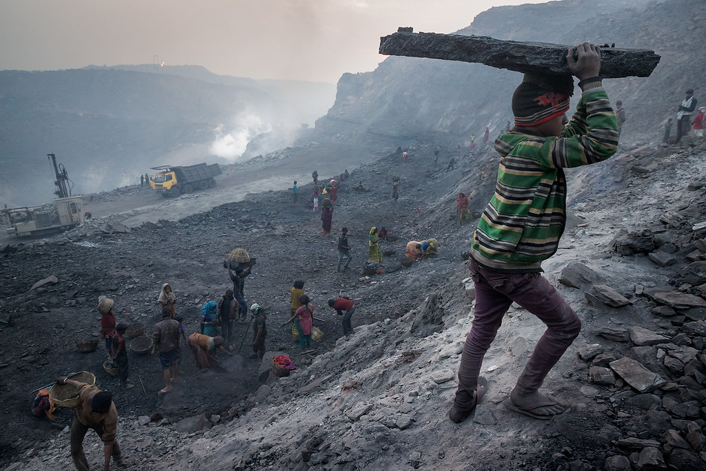 Every morning at least a hundred people carry away illegally collected coal from several coalmines. Also a lot of children do this work. <br /> Young boy carrying coal on his head.
