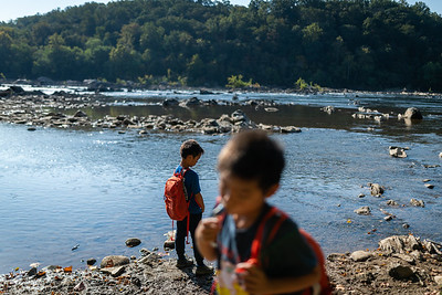 Henry Pham, 9, (left) looks at bugs in the water, as Hayle Pham, 7, (right) sips water from his backpack at Carderock, Md. on Sept. 29, 2019.