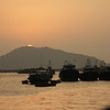 A picturesque sunset seen from cafeterias along the coastal road on Cheung Chau. The sun sets behind the hills of Lantau Island.